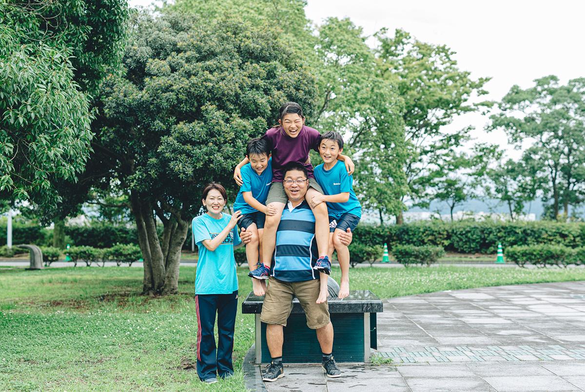 子ども3人を肩に乗せるお父さんとそばで佇むお母さん