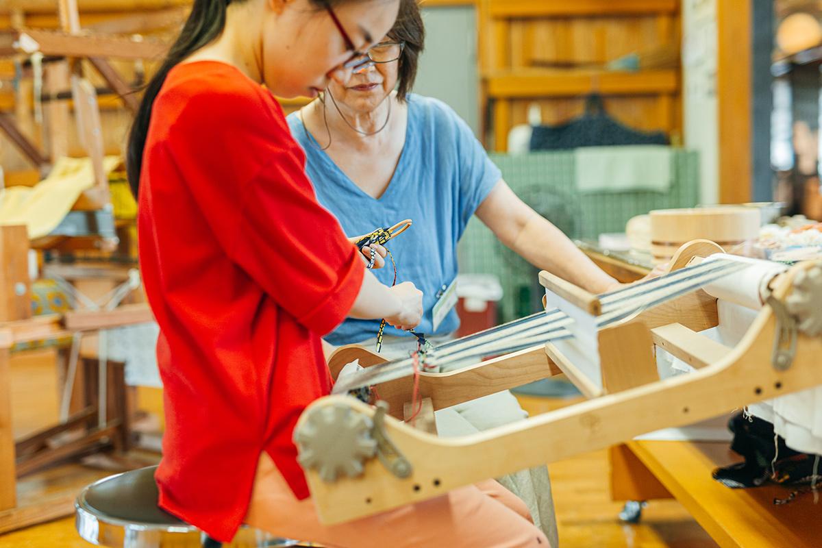 工芸館で女性に織物を教わる少女