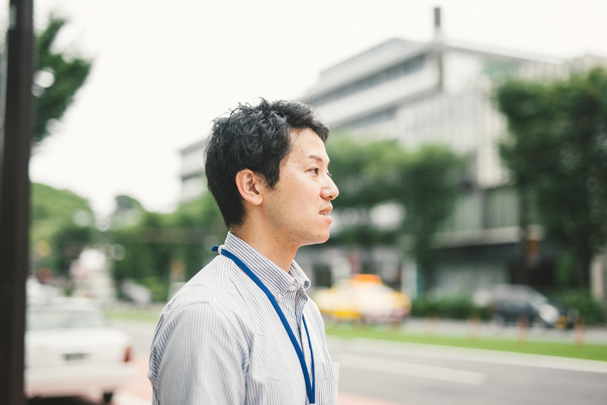 市街地で遠くを見つめる男性の横顔