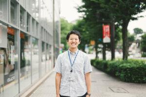 緑あふれる市街地に立つ、笑顔の男性