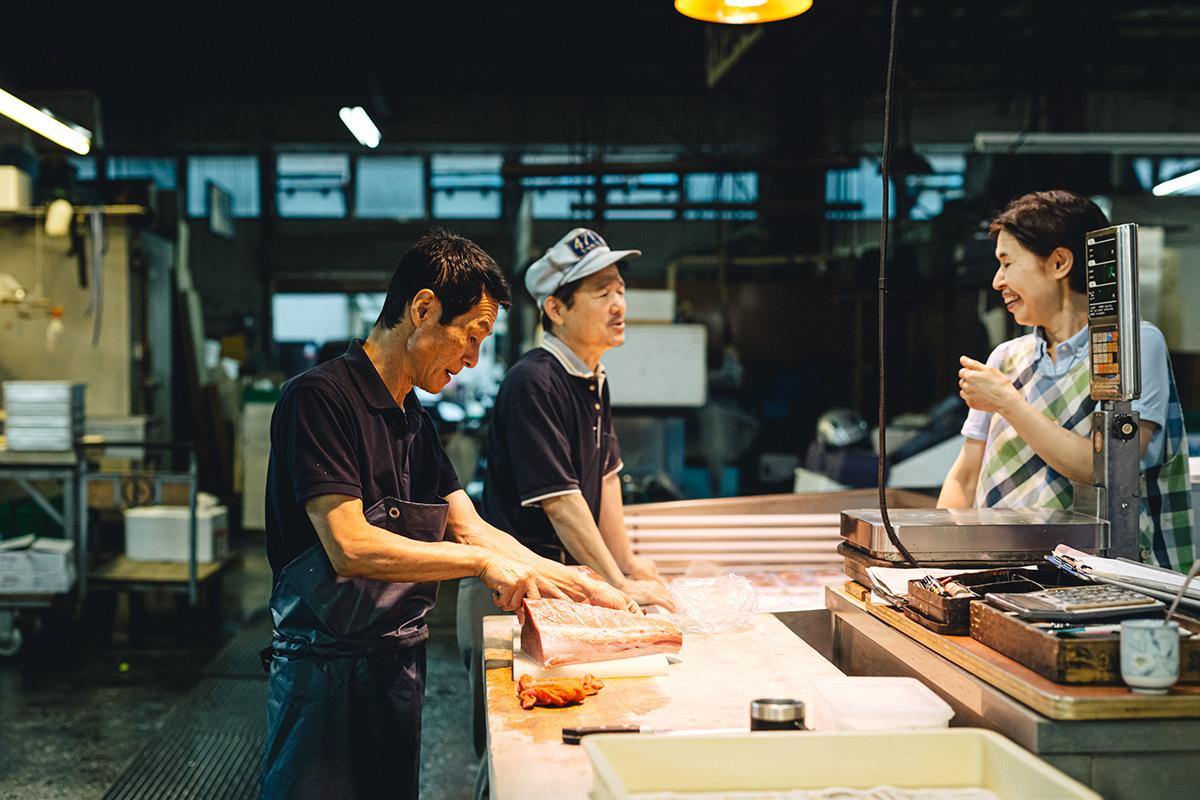 田崎市場にて談笑しつつ仕事する男性二人と女性