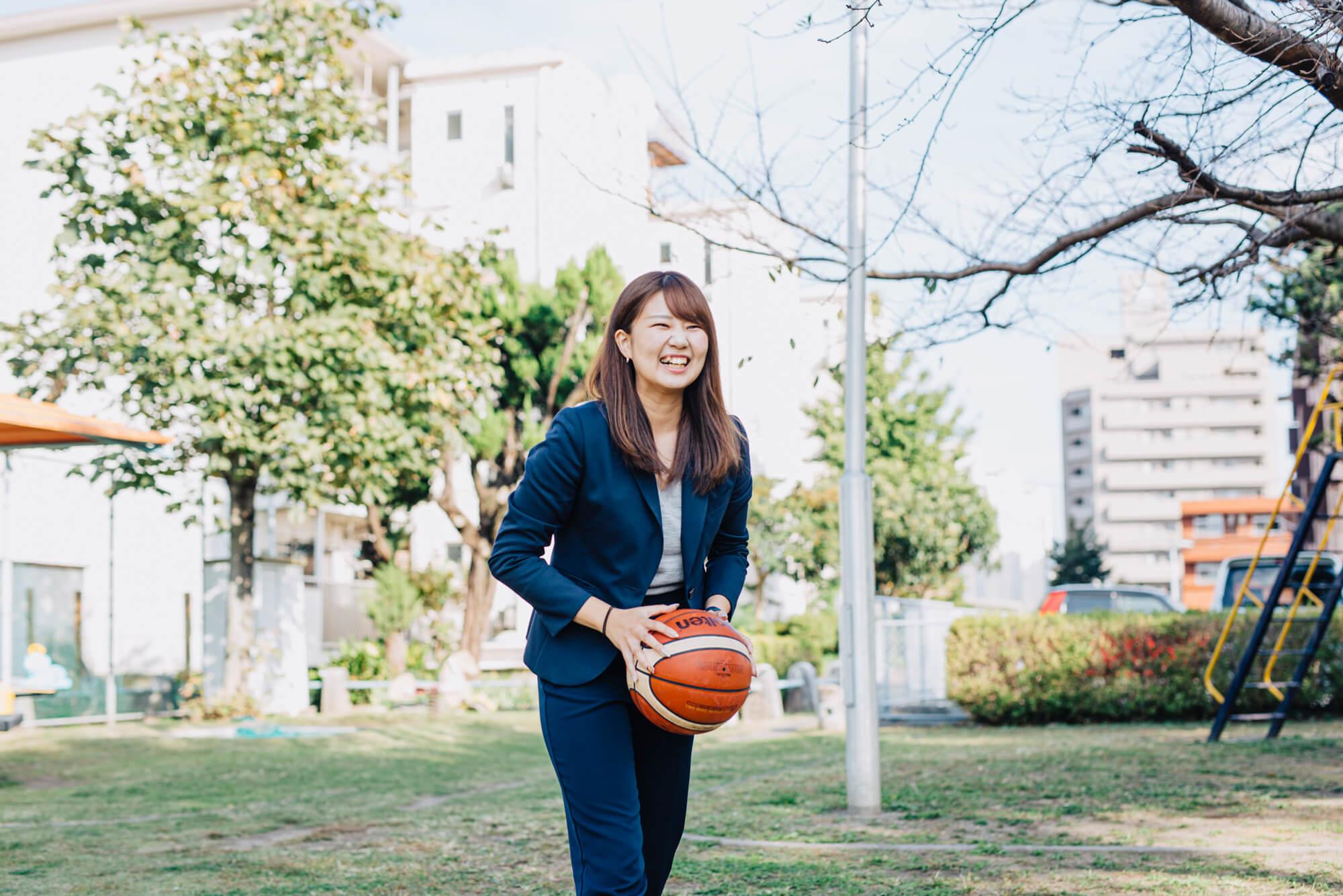 公園でバスケットボールを楽しむ女性