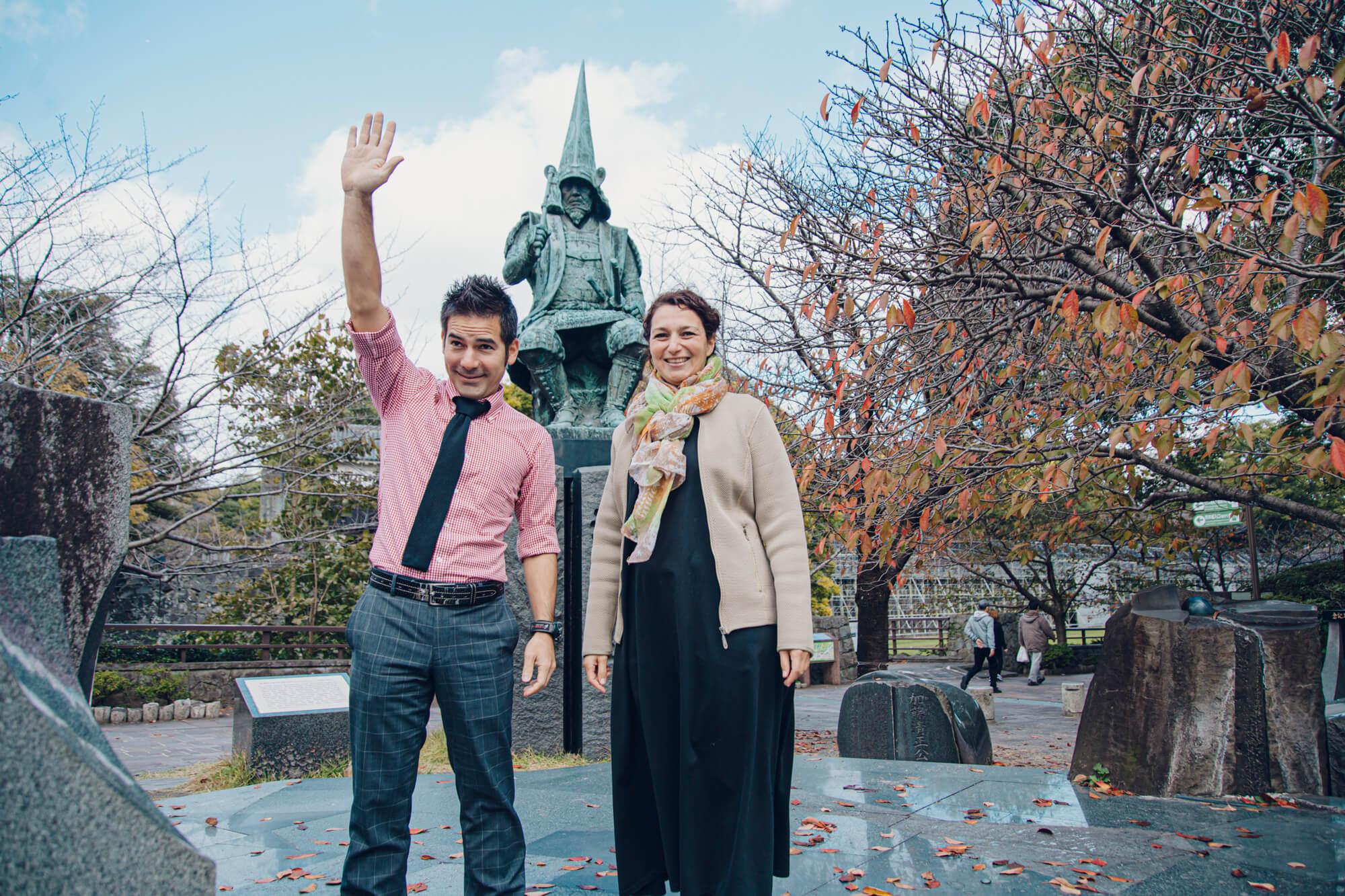 銅像の前に立つ男女